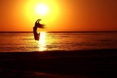 跳跃在日落的女孩的剪影 免版税库存照片