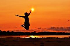 跳跃在日落的妇女的剪影,接触 库存图片