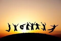 跳跃在日落的小组十几岁 免版税库存照片