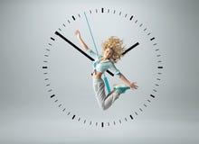 跳跃在时钟的白肤金发的运动员 免版税库存图片