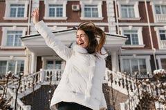 跳跃在晴朗的冬日的被启发的妇女,享受圣诞节假日 滑稽的女性模型室外照片在白色的 免版税库存照片