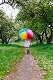 跳跃在有五颜六色的彩虹伞的开花的庭院里的一件白色礼服的女孩 春天,户外 免版税库存照片