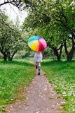 跳跃在有五颜六色的彩虹伞的开花的庭院里的一件白色礼服的女孩 春天,户外 库存图片