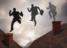 跳跃在有剧烈的轻的多云天空的屋顶的商人剪影 图库摄影