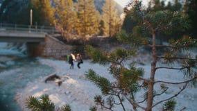 跳跃在有背包和吉他的岩石河附近的两年轻女人在山的一座桥梁下 影视素材