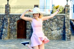 跳跃在有花的一个帽子的愉快的女孩在一件桃红色礼服 免版税库存照片