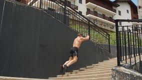 跳跃在楼上在楼梯和做准备在奔跑前的年轻人运动员 股票录像