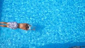 跳跃在水池和飞溅透明的水的年轻人顶视图 游泳在水下的无法认出的人  股票录像