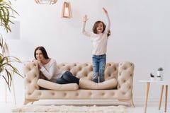 跳跃在沙发的正面愉快的女孩 免版税库存图片