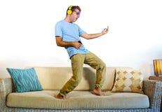 跳跃在沙发长沙发的年轻愉快和激动的人听到与演奏Air Guitar疯狂的hav的手机和耳机的音乐 免版税库存图片