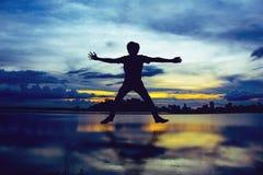 跳跃在河沿的日落的人剪影 免版税图库摄影