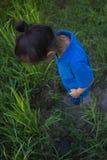 跳跃在泥泞的水坑的亚洲儿童游戏在米领域 免版税库存照片