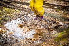 跳跃在泥泞的水坑的逗人喜爱的小女孩 免版税库存图片