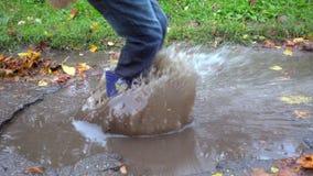 跳跃在泥泞的水坑,慢动作的年轻男孩 影视素材