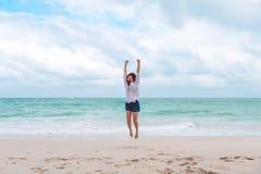 跳跃在海前面的海滩的妇女有感到的愉快 免版税库存图片