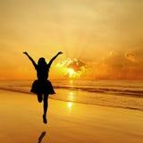 跳跃在海日落的愉快的妇女 免版税库存图片