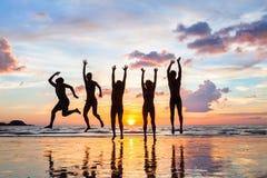 跳跃在海滩在日落,愉快的朋友剪影的人  图库摄影