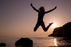 跳跃在海滩的愉快的少妇在日落 免版税图库摄影