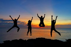 跳跃在海滩的朋友和配合剪影在成功事务的日落时间 免版税库存照片