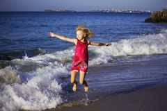 跳跃在海滩的波浪的色的礼服的愉快的女孩 图库摄影
