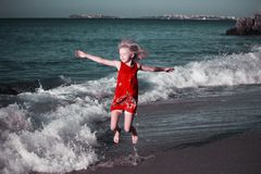 跳跃在海滩的波浪的色的礼服的愉快的女孩 免版税库存图片