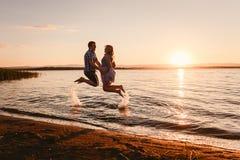 跳跃在海的人和女孩在日落 免版税库存图片
