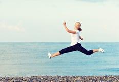 跳跃在海的海滩的愉快的年轻美丽的妇女 免版税库存图片