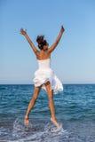 跳跃在海边的愉快的妇女 免版税库存图片