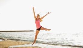 跳跃在海边,体操运动员女性做的美丽的运动的妇女 免版税库存图片