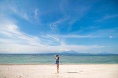跳跃在海滩机智白色沙子的愉快的女孩 热带海岛努沙Lembongan,印度尼西亚 库存图片