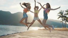 跳跃在海滩的三个朋友在日落 股票视频