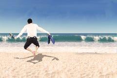 跳跃在海滩的商人后侧方 免版税库存图片