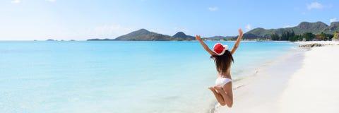 跳跃在海滩的圣诞老人帽子和比基尼泳装的妇女 库存图片