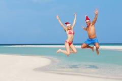 跳跃在海滩的夫妇戴圣诞老人帽子 库存图片
