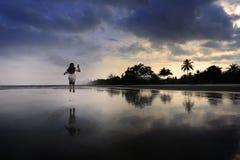 跳跃在海滩的女孩 免版税库存照片