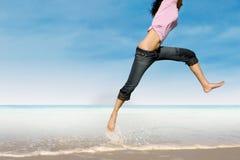 跳跃在海滩的妇女特写镜头 免版税库存图片