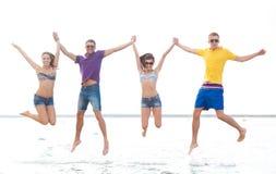 跳跃在海滩的小组朋友或夫妇 免版税库存图片
