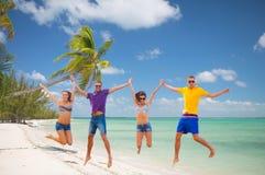 跳跃在海滩的小组朋友或夫妇 库存图片