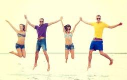 跳跃在海滩的小组朋友或夫妇 库存照片