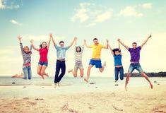 跳跃在海滩的小组朋友 免版税图库摄影