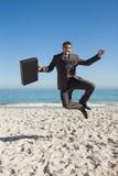 跳跃在海滩的快乐的商人 库存照片