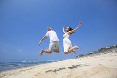 跳跃在海滩的愉快的夫妇 免版税图库摄影
