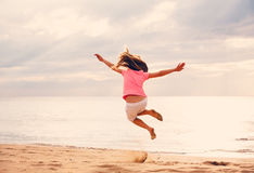 跳跃在海滩的愉快的女孩在日落 免版税图库摄影