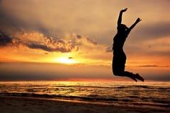 跳跃在海滩的愉快的妇女在日落 免版税库存照片