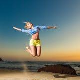 跳跃在海滩的愉快的少妇 库存照片