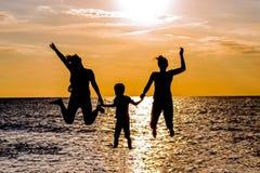 跳跃在海滩的母亲和孩子剪影在日落 免版税库存照片