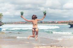 跳跃在海滩的比基尼泳装的性感的小姐用新鲜的未加工的健康菠萝果子 愉快的假期概念 巴厘岛 库存图片