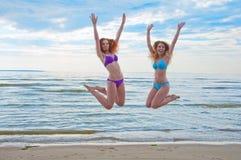 跳跃在海滩的比基尼泳装的愉快的激动的少妇 免版税库存照片