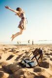 跳跃在海滩的青少年的女孩在天时间 免版税库存图片