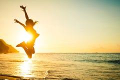 跳跃在海滩的青少年的女孩 免版税库存图片